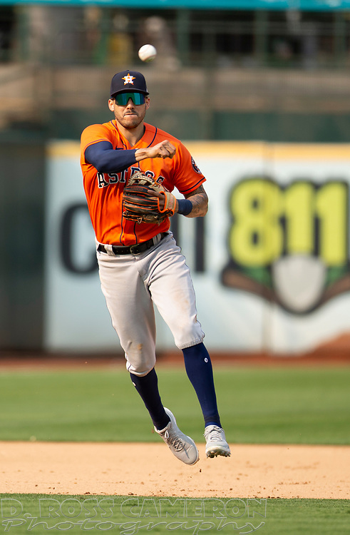 Sep 25, 2021; Oakland, California, USA; Houston Astros shortstop Carlos Correa (1) leaves his feet to throw out Oakland Athletics catcher Sean Murphy at first base during the eighth inning at RingCentral Coliseum. Mandatory Credit: D. Ross Cameron-USA TODAY Sports