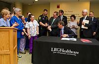 Laconia Police Chief Matt Canfield receiving the pen from Governor Chris Sununu following the signing of Bill 376 on Thursday morning at Lakes Region General Hospital.  (Karen Bobotas/for the Laconia Daily Sun)