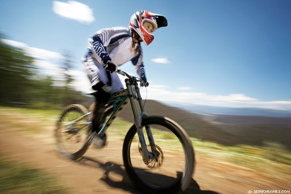 A downhill mountain biker builds speed on the trail in Winter Park, CO.