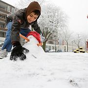 Nederland Rotterdam 21 december 2007 ..Jongetje maakt sneeuwpop Kinderen spelen in de sneeuw op het Noordereiland  .Foto David Rozing