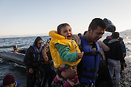 A father and holds his child as they arrive in Europe via a boat from Turkey. The number of refugees and migrants arriving to Europe in October 2015 was equal to the total arrivals of 2014 according to UNHCR figures.