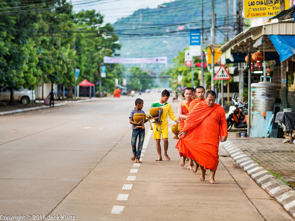 16 JUNE 2016 - PAKSE, CHAMPASAK, LAOS: Buddhist monks walk back to Wat Luang after the morning Tak Bat, or alms rounds in Pakse. The monks walk through the community just after sunrise accepting alms from people. Pakse is the capital of Champasak province in southern Laos. It sits at the confluence of the Xe Don and Mekong Rivers. It's the gateway city to 4,000 Islands, near the border of Cambodia and the coffee growing highlands of southern Laos.      PHOTO BY JACK KURTZ
