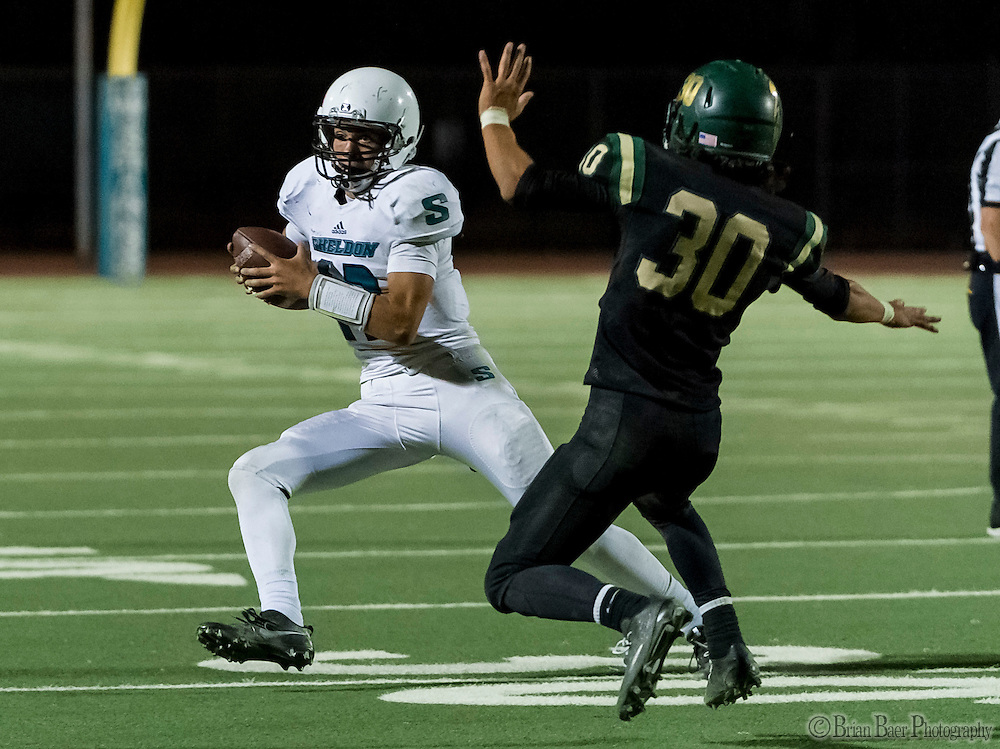 Sheldon High School Husky Chancellor Lachapelle (12), runs with the ball as Monterey Trail Mustangs Aztlan Lopez (30), defends during the third quarter as the Monterey Trail Mustangs host the Sheldon High School Huskies Friday Sep 23, 2016. Sheldon won the game 27-22.<br /> photo by Brian Baer