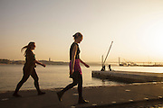 Two ladies walking by Tagus riverside at sunset in Lisbon