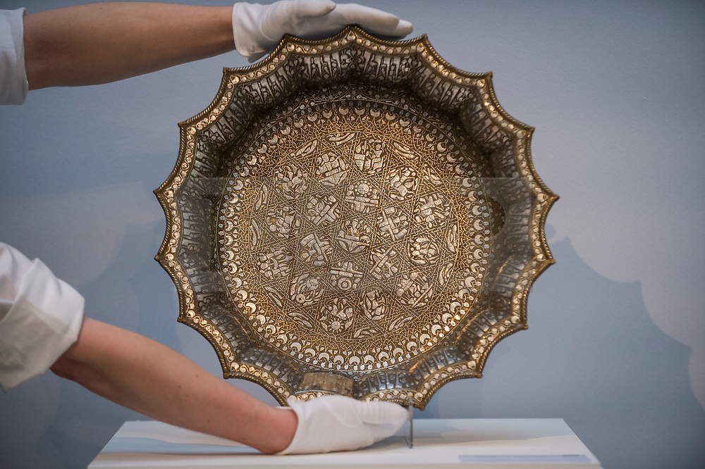 "© Licensed to London News Pictures. 29/03/2021. LONDON, UK. A technician presents ""a magnificent twelfth-century silver-inlaid scalloped basin adorned with astrological designs"" (est. £1,000,000-1,500,000).  Preview of the upcoming Arts of the Islamic World & India sale where historic objects, paintings and manuscripts from the last 1,000 years are to be auctioned on 31 March at Sotheby's New Bond Street galleries.  Photo credit: Stephen Chung/LNP"