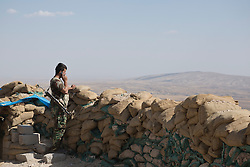 © Licensed to London News Pictures. 01/09/2015. Bashiqa, Iraq. A Kurdish peshmerga fighter uses his mobile phone as he keeps watch from a position on top of Bashiqa Mountain near Mosul, Iraq.<br /> <br /> Bashiqa Mountain, towering over the town of the same name, is now a heavily fortified front line. Kurdish peshmerga, having withdrawn to the mountain after the August 2014 ISIS offensive, now watch over Islamic State held territory from their sandbagged high-ground positions. Regular exchanges of fire take place between the Kurds and the Islamic militants with the occupied Iraqi city of Mosul forming the backdrop.<br /> <br /> The town of Bashiqa, a formerly mixed town that had a population of Yazidi, Kurd, Arab and Shabak, now lies empty apart from insurgents. Along with several other urban sprawls the town forms one of the gateways to Iraq's second largest city that will need to be dealt with should the Kurds be called to advance on Mosul. Photo credit: Matt Cetti-Roberts/LNP