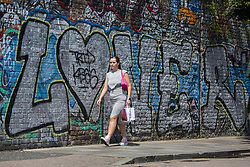 © Licensed to London News Pictures.  13/07/2021. London, UK. A Members of the public walks in Shoreditch, east London as the sun comes out after a few weeks of rainy weather. Photo credit: Marcin Nowak/LNP