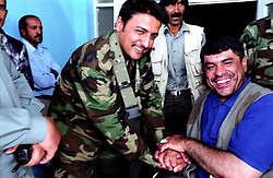 KABUL 25 August 2005..The President of Paralympic Federation Mr Abdul Rahman, wearing a blue t-shirt, shakes hands with the head of Afghan Security at Ghazi Stadium.....On 23-25 August 2005, Special Olympics Afghanistan held its first national Games at Olympic Stadium in Kabul. ..More than 300 athletes, including 80 female athletes, experienced a taste of happiness and achievement for the first time in their lives. They competed in athletics, bocce and football (soccer). Because of cultural restrictions, males and females competed at separate venues...