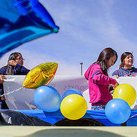 Caileigh Bitsoi, left, Kayla Russell and Darcy hang balloons and banners on a float for a parade in Sanders Friday.