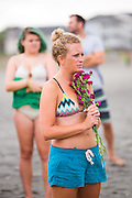 Charleston area surfers gather for a moment of silence before holding a traditional memorial paddle out to honor and remember the nine people killed at the historic mother Emanuel African Methodist Episcopal Church June 27, 2015 in Folly Beach, South Carolina. Earlier in the week a white supremacist gunman killed 9 members at the historically black church.