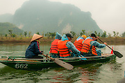 Traveling through Tam Coc caves on the Ngo Gong River in Ninh Binh, Vietnam