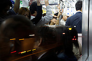 evening commuters in a jam packed train reflecting in window with streaks of traffic light