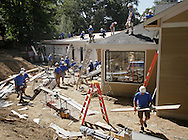 """Volunteers works on the rear of the new home being constructed for the Korpai family on Monday, Aug. 22, 2011. The construction will be featured on an episode of """"Extreme Makeover: Home Edition""""."""