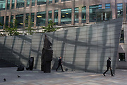 Two men and two pigeons walk in reflected light and modern architecture at Broadgate, on 10th May 2017, in the City of London, England.