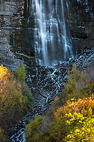 Bridal Veil Falls in Utah's Provo Canyon cascades down the mountainside as the reamining Fall colors brighten up the hillside.