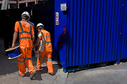 Workmen in hi-visibility clothing carry a blue wiring reel, coincidentally the same colour as a construction container. Walking along the street in the City of London, the capital's financial heart, they have turned a corner, around the deep blue-painted container on their works site, a construction site on the huge Crossrail project that is transforming London's deep underground rail system.