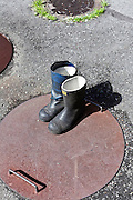 black rubber boots standing on a rusty metal manhole cover