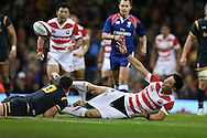Akihito Yamada of Japan gets his pass away despite getting his shorts pulled down by Lloyd Williams of Wales. .  Under Armour 2016 series international rugby, Wales v Japan at the Principality Stadium in Cardiff , South Wales on Saturday 19th November 2016. pic by Andrew Orchard, Andrew Orchard sports photography