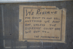 management sign posted on a screen door of an abandoned store in New Mexico