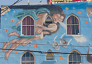 A portion of a colorful mural on the side of a building in Venice, California depicts a man with a aqua-colored cape holding a woman as they fly through the air.
