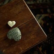 Two heart shaped rocks on a wood stool