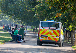 "© Licensed to London News Pictures. 15/09/2020. London, UK. Members of the public take a rest in the  warm sunshine this morning as Police vans patrol Hyde Park enforcing the ""Rule of Six"" as the mini-heatwave continues in the South East of England with highs of 29c. Prime Minister Boris Johnson announced last week that gatherings of more than six people will be banned from Monday (yesterday) in the hope of reducing the coronavirus R number. The Rule of Six has already become unpopular with MPs and large families for being too strict. Photo credit: Alex Lentati/LNP"