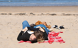 Portobello, Scotland, UK. 25 April 2020. Views of people outdoors on Saturday afternoon on the beach and promenade at Portobello, Edinburgh. Good weather has brought more people outdoors walking and cycling. Police are patrolling in vehicles but not stopping because most people seem to be observing social distancing. Couple cuddling on the beach.  Iain Masterton/Alamy Live News