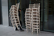 Stack of chairs outside a hotel in the City of London, UK. A worker delivering chairs stack by stack and placing them in a block.