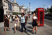 Visitors to Trafalgar Square walk past the National Gallery and a red phone box.