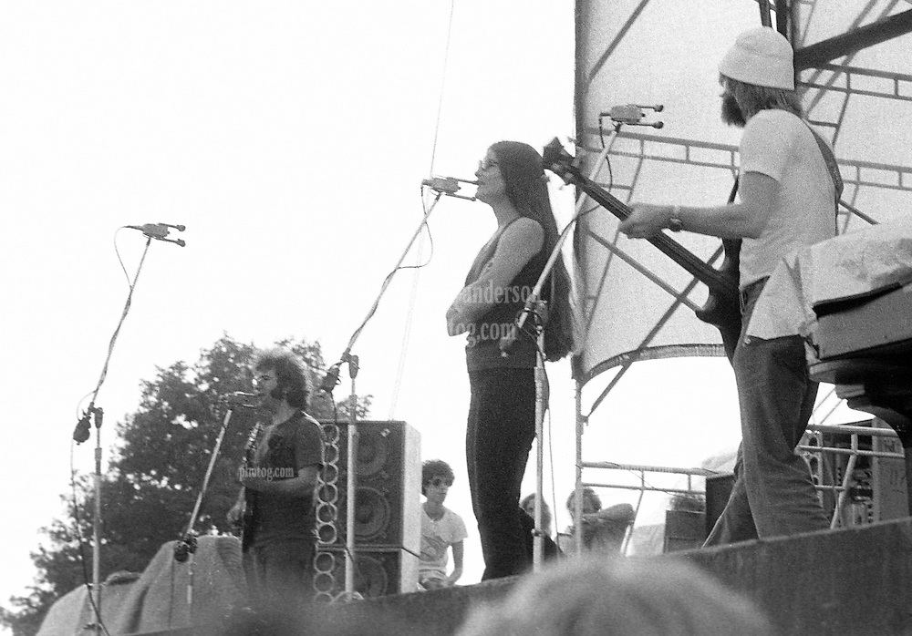 Jerry Garcia, Donna Jean Godchaux and Phil Lesh with Ned Lagin watching from the wing. Grateful Dead Live at Dillon Stadium, Hartford, CT 31 July 1974 featuring the Wall of Sound. Photo taken as the first set gets underway.