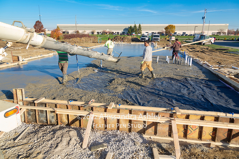 Building crew smoothes wet cement as it is released from chute at site of new physical therapy and wellness center building construction project.