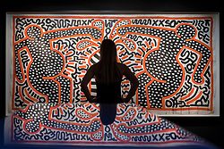 """© Licensed to London News Pictures. 28/06/2018. LONDON, UK. A gallery staff member poses against """"Untitled (May24-83)"""", 1983, by Keith Haring.  Members of the public visit Masterpiece London, the world's leading cross-collecting art fair held in the grounds of the Royal Hospital Chelsea.  The fair brings together 160 international exhibitors presenting works from antiquity to the present day and runs 28 June to 4 July 2018.  Photo credit: Stephen Chung/LNP"""