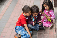 Two boys and a young girl playing on the street in Cotacahci, Ecuador
