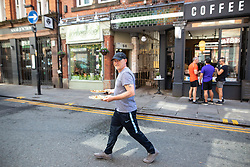 © Licensed to London News Pictures . 20/05/2020 . Manchester , UK . A man carries two plates of cooked food from Rustica Sandwich Bar in Manchester City Centre . On the hottest day of the year so far independently run coffee shops and bars are open and trading with social distancing measures applied , after a period of being shut in an effort to reduce the spread of Covid-19 . Photo credit : Joel Goodman/LNP