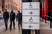 Two disability access signs outside the British Library, London, United Kingdom.  One guides the way to the accessible staff entrance and the other for the public entrance.  The signs use the International Symbol of Access designed in 1968. The symbol is often seen where access has been improved, particularly for wheelchair users, but also for other disability issues.  Frequently, the symbol denotes the removal of environmental barriers, such as steps, to help also older people, parents with baby carriages, and travelers.