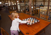 Olivia spends some quiet time at the chess table during Wednesday morning's Story Time session at the Gilmanton Year Round Library.  (Karen Bobotas/for the Laconia Daily Sun)