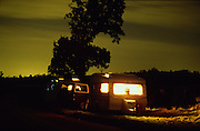Caravan and trailer at night on a grassy roadside bank. Romany gypsies, Leslie and Edna traveling with a traditional bowtop wagon in the English countryside...English Romany Gypsies traditionally traveled the country roads camping nearby towns and villages, choosing the grassy roadside banks, where they tethered their horses, or in farmer's fields, when they were allowed. Travelling in bowtop wagons drawn by horses, and before that with tents, sometimes with horse drawn carts or just by foot. Often they worked as casual agricultural labourers, doing the seasons work. They also could earn their living in different ways, sometimes selling their wares, brass, tin, wood and cloth, such as embroidered cloths or lace, telling fortunes, music and dancing, and through crafts skills in basket making, plaiting chair bases, sharpening knives,  They would make fires from old wood, cleaning up after them when they moved on. There were several horse fairs, notably Appleby in Cumbria and Stow-on-Wold in the Cotswolds where they trade and sell horses, some traditions which keep to this day.