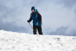© Licensed to London News Pictures. 04/12/2020. <br /> A man pictured walking on Penyfan, in the Brecon Beacons, the highest point in southern Wales and England, which has seen it's first snowfall of the year. Photo credit: Robert Melen/LNP