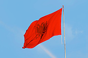 The Albanian flag banner, red with a black double headed eagle, against a blue sky. The Tirana Main Central Square, Skanderbeg Skanderburg Square. Tirana capital. Albania, Balkan, Europe.
