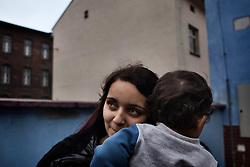 "Veronika Sindelárová holds her youngest child Fabián Gina, 1, outside their home in Ostrava, Czech Republic on March 1, 2012. Veronika was one of 18 Roma children who were represented in the D.H. and Others v. Czech Republic case, the first challenge to systemic racial segregation in education to reach the European Court of Human Rights. When this case was first brought in 2000, Roma children in the Czech Republic were 27 times more likely to be placed in ""special schools,"" intended for the mentally disabled, than non-Roma children. In 2007, the Grand Chamber of the European Court of Human Rights ruled that this pattern of segregation violated nondiscrimination protections in the European Convention on Human Rights. Despite this landmark decision, little change has occurred: the ""special schools"" have been renamed but follow the same substandard curriculum and Roma continue to be assigned to these schools in disproportionate numbers. The process of integration has barely begun."