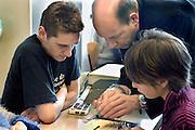 Nederland, Nijmegen, 23-2-2005een jongen en een meisje, leerlingen voortgezet onderwijs, krijgen uitleg van een leraar, docent over een elektronische schakeling. Natuurkunde, informatica, computertechniek, elektronica, exacte vakken, beta vak, betavakFoto: Flip Franssen/Hollandse Hoogte