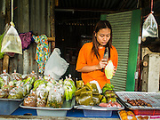 """04 FEBRUARY 2015 - BANGKOK, THAILAND:  A street food vendor grates unripened papaya to make """"som tam"""" or Thai papaya salad, in central Bangkok. After months of relative calm following the May 2014 coup, tensions are increasing in Bangkok. The military backed junta has threatened to crack down on anyone who opposes the government. Relations with the United States have deteriorated after Daniel Russel, the US Assistant Secretary of State for Asian and Pacific Affairs, said that normalization of relations between Thailand and the US would depend on the restoration of a credible democratically elected government in Thailand.   PHOTO BY JACK KURTZ"""
