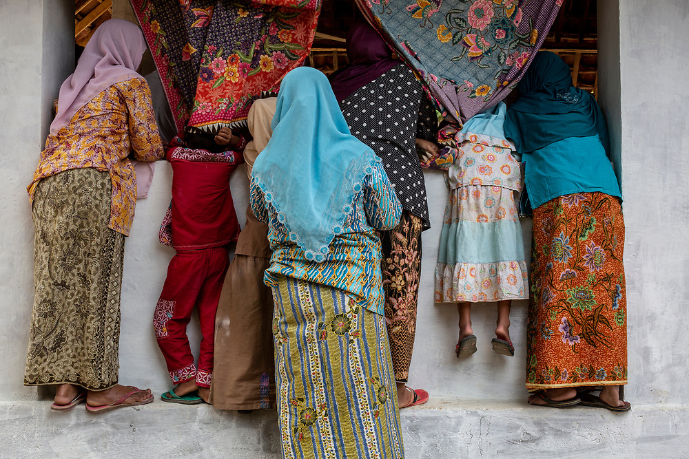 Villagers watch as their friends and family demonstrate the batik tulis (handmade batik) making process to tourists. The entire village produces batik of the finest quality and most vibrant colors by using a batik process of applying wax and dyes to fabric to create intricate and detailed designs by hand. Podhek Village in Pamekasan, Madura  October 20, 2018