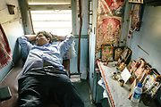 The kitchen manager takes a nap in his compatrment that is adorned with a mandir, or Hindu shrine.<br /> Inside the Dibrugarh-Kanyakumari Vivek Express, the longest train route in the Indian Subcontinent. It joins Kanyakumari, Tamil Nadu, which is the southernmost tip of mainland India to Dibrugarh in Assam province, near the border with Burma.