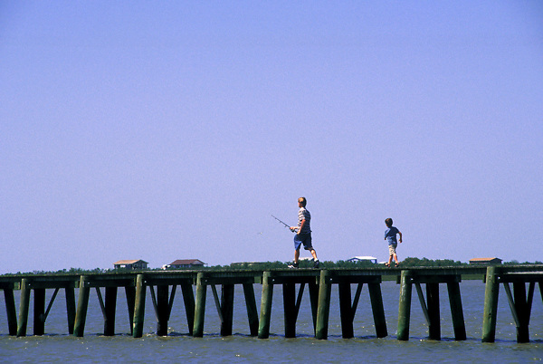 Stock photo of boys running to the end of the pier to cast their lines.