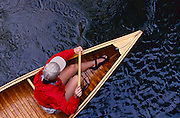 "A young woman in a bright red jacket paddles a vintage wooden canoe in a stream. MODEL RELEASED - To license this image, click on the shopping cart below - -- Determine pricing and license this image, simply by clicking ""Add To Cart"" below -- A fit young woman in a red jacket and a cap paddles a vintage canoe in fast moving water. MODEL RELEASED"