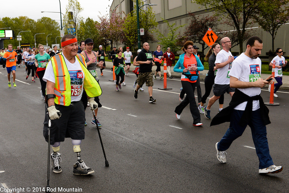 Vancouver, BC, Canada - April 27, 2014 - A competitive and triumphant man with prosthetics seen running along Burrard Street during the 2014 Vancouver Sun Run.The Vancouver Sun Run is an annual event sponsored by the Vancouver Sun newspaper and one of the largest road races in the world.<br /> <br /> Photo: © Rod Mountain<br /> <br /> http://www.rodmountain.com<br /> <br /> @rod_mountain