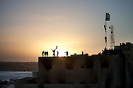 Protesters cheer ontop of the Tabrurk police station at the central town square on Feb. 24, 2011. The square has become a symbol of New Libya, tents have been set up, people are giving out free food, and heavy equiptment is being used to repair the square.