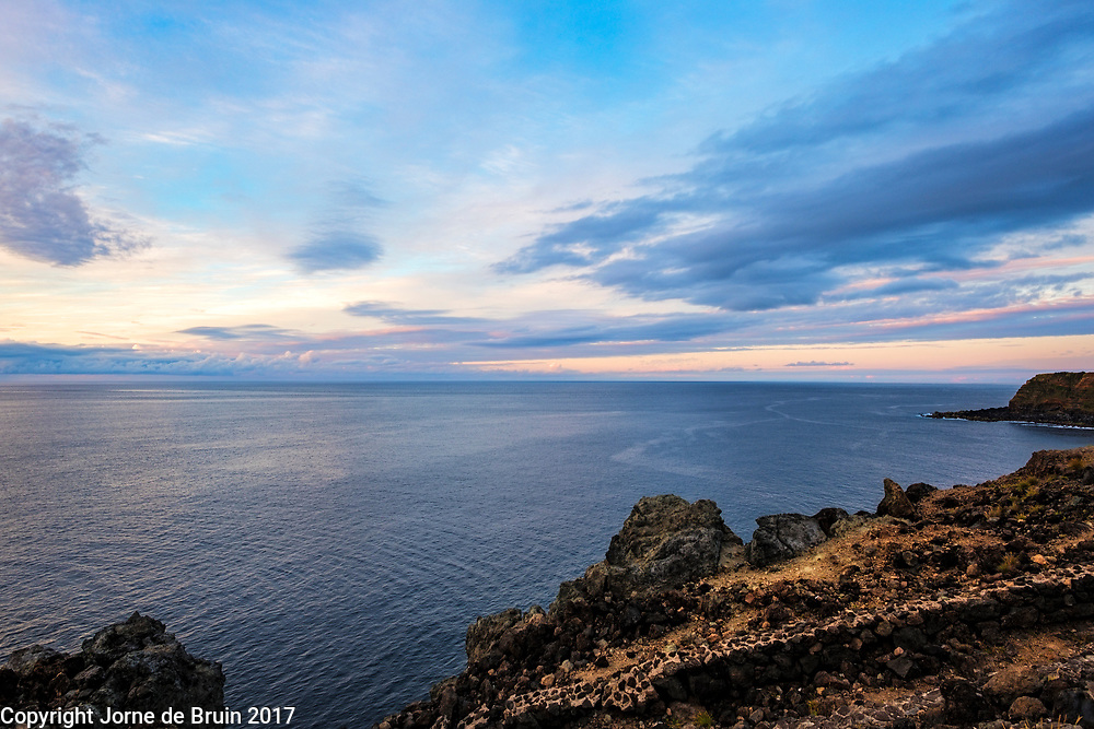 Sunset over Atlantic at the rocky shore of Terceira, Azores, Portugal.