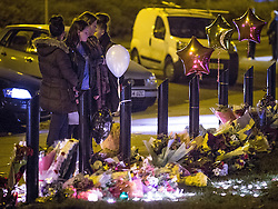 © Licensed to London News Pictures . 28/11/2013 . Bolton Road , Salford , UK . Young friends of 18-year-old moped crash victim , Tom Ackerley , who was killed in a crash last night (27th November 2013) , hold a candlelit vigil at the scene of the crash , this evening (28th November 2013) . Tom Ackerley was killed when riding his moped , in a crash involving a taxi and a Vauxhall Astra , in Salford, Greater Manchester , last night (27th November 2013) . Photo credit : Joel Goodman/LNP